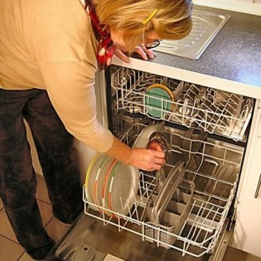 Frau an Spülmaschine